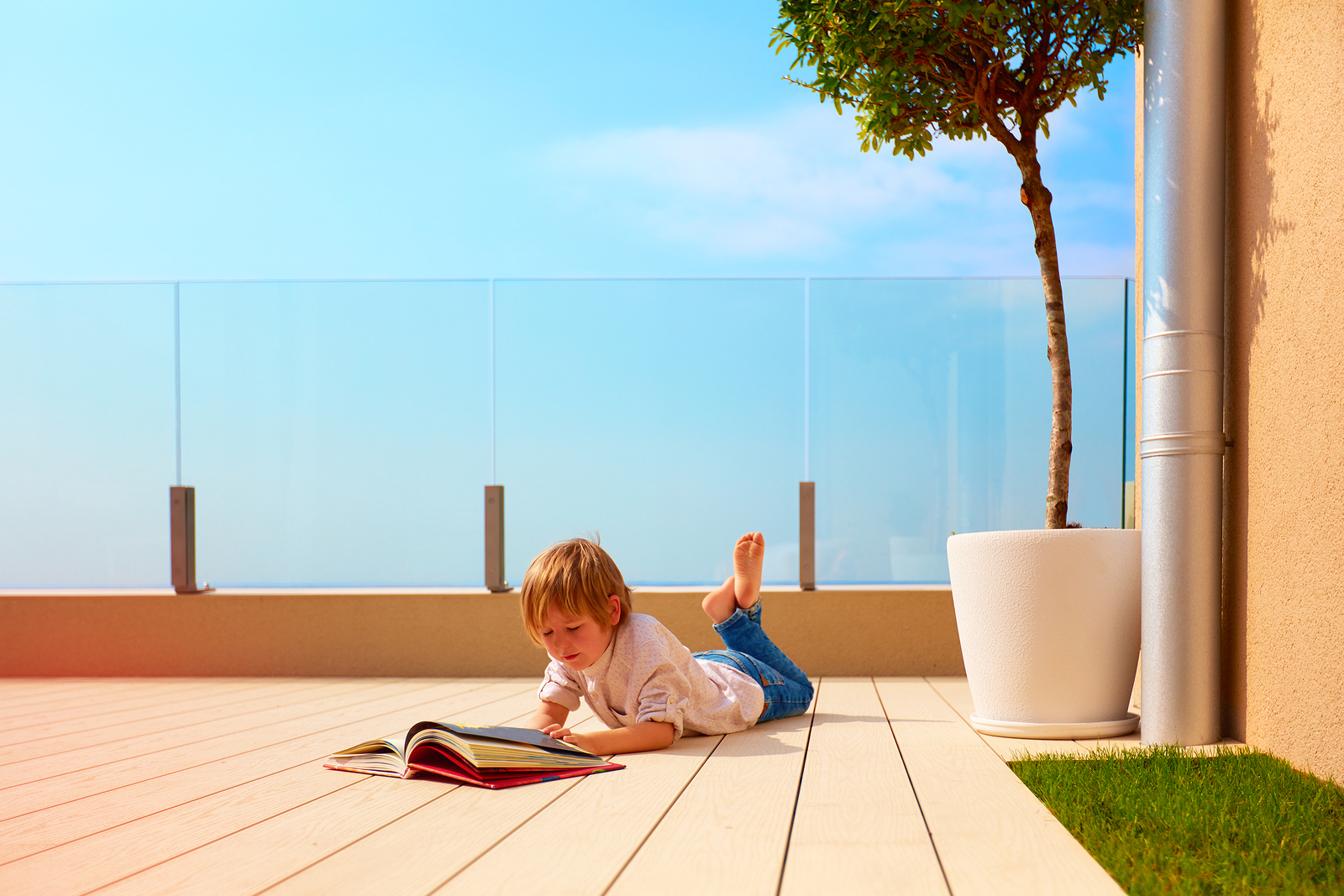 Young Boy, Kid Reading Book On Rooftop Terrace, While Lying Down