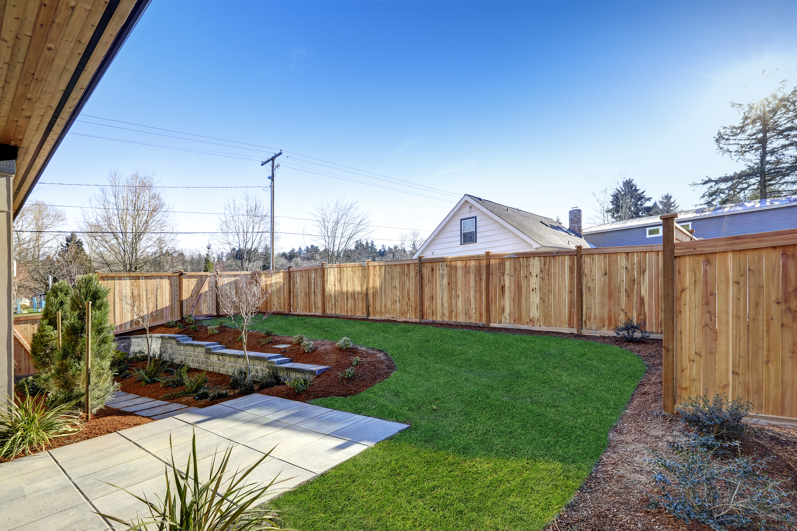 Sloped Backyard Surrounded By Wooden Fence Luxury New Constructi